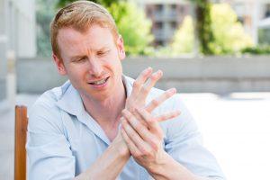 Junger Mann knacken Gelenke Hand